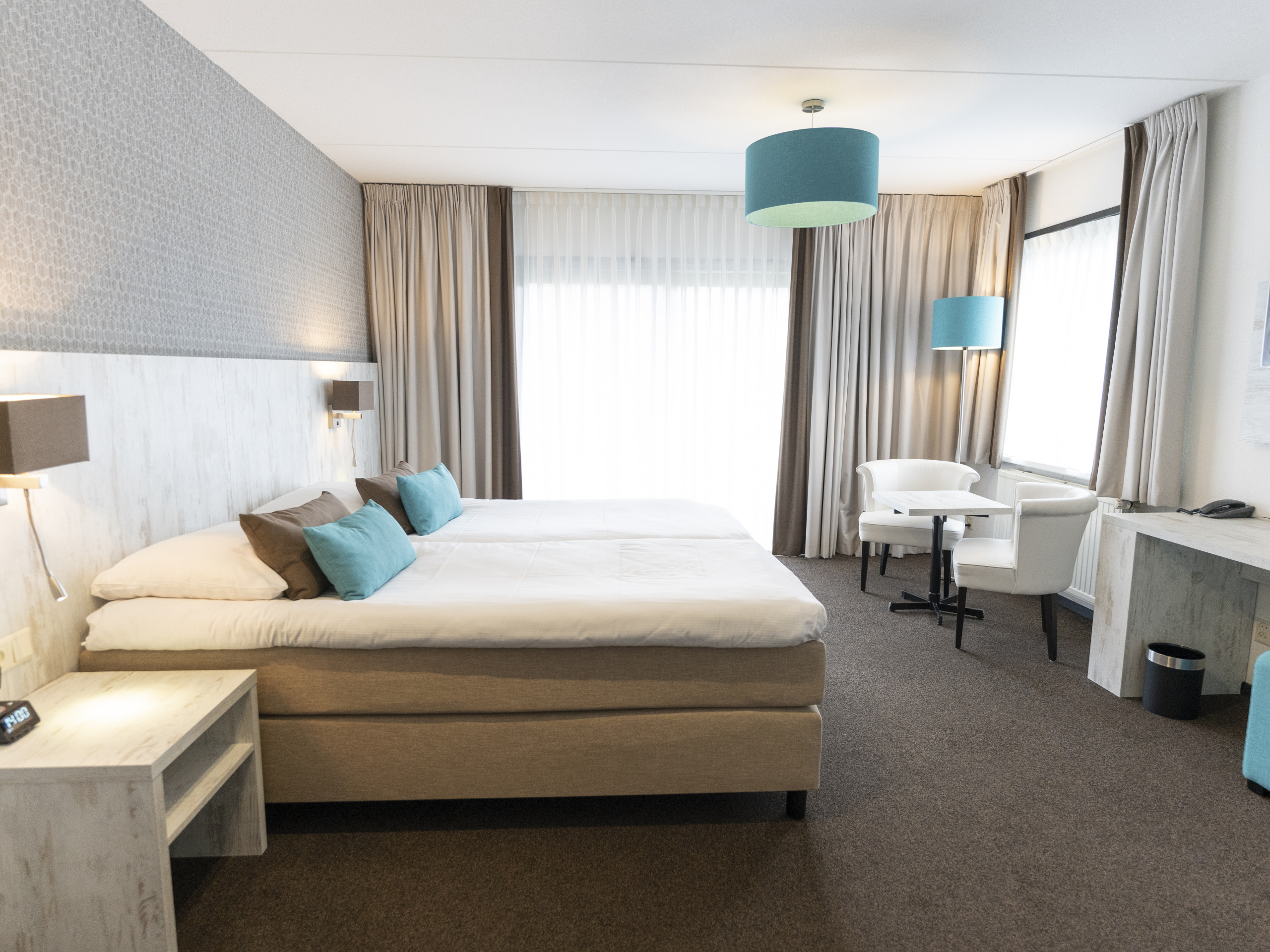 Hotel room with extra sitting area with comfy chairs near De Koog